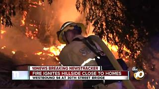 Fire ignites hillside close to homes - Video