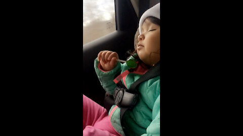 Sleepy baby licks her lollypop to sleep