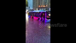 Hero bus driver helps passengers off bus stuck on flooded street - Video