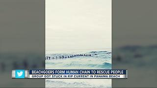 Beachgoers form human chain to rescue family in water - Video