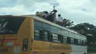 Indian school children risk lives by riding on bus roof - Video