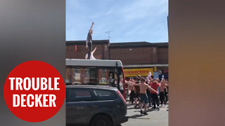 England fans celebrating by surfing on a bus