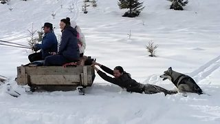 Hilarious moment man uses dog as a sleigh - Video