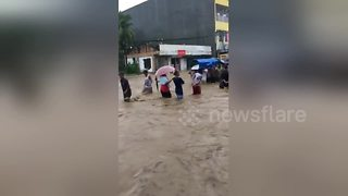 Mourners carry coffin through flooded street in the Philippines - Video