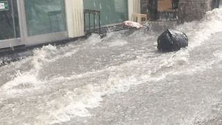 Torrents of Floodwater Carry Trash Bags Down Street Near Istanbul's Grand Bazaar - Video