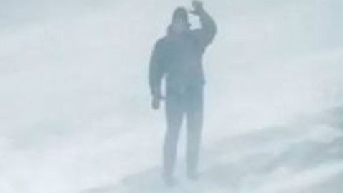 Bostonian Trudging Through Snow Waves to Camera During Blizzard