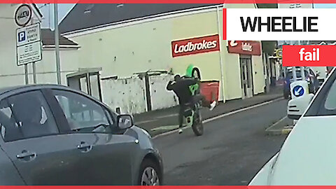 Idiot motorist falls off motorbike without any protective gear after attempting a wheelie