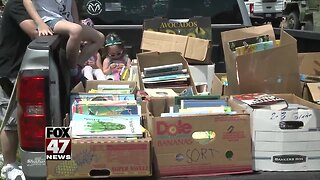 Volunteers pass out books to kids during Memorial Day parade