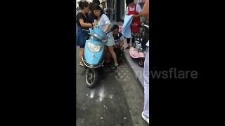Woman on scooter gives birth in street - Video