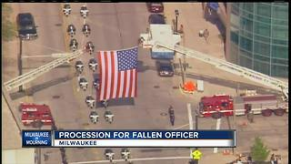 Community pays respects to officer at procession - Video