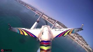 Daredevil pilot flies upside down over French marina - Video