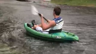 Young man goes kayaking on flooded street