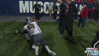 Arizona Wildcats quarterback runs over Miss Arizona on sideline during game