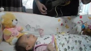 Baby girl captivated by her dad's guitar playing