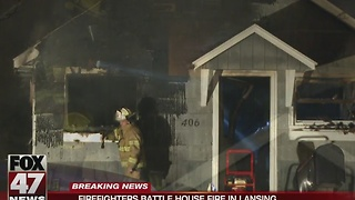 Firefighters battle house fire in Lansing - Video