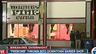 Police are investigating a firebomb thrown through a window at a barber shop