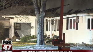 Firefighters battle house fire in Delta Township - Video