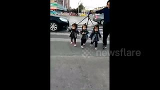 Grandfather holds triplets with leads to cross road - Video