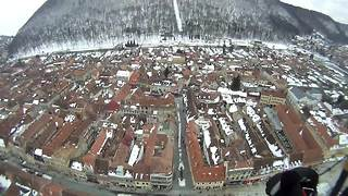 Paragliding above a snow-covered city in Transylvania - Video