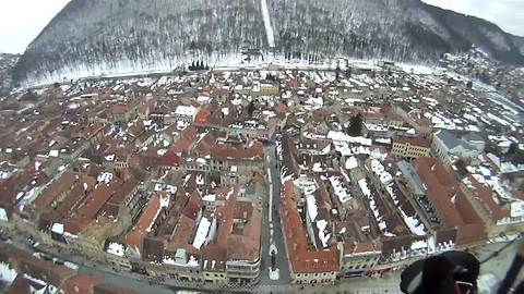Paragliding above a snow-covered city in Transylvania