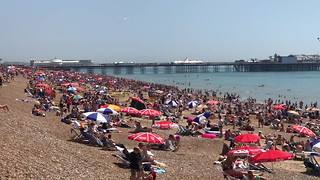 Thousands gather on Brighton beach on hottest day of the year - Video