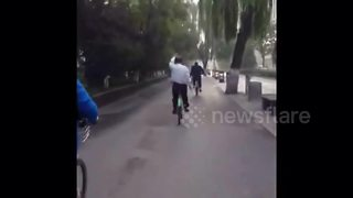 Chinese man does Tai Chi while riding bike on busy road - Video