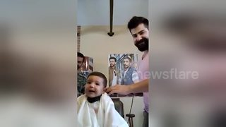 Baby gets first haircut and really enjoys it - Video