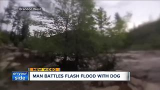 Man battles flash flood with dog - Video