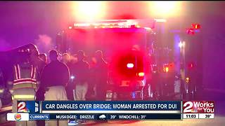 Woman arrested after car dangles off bridge