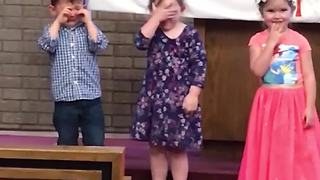 """Little Girl Facepalms when Little Boy Cries at Kids' Concert"""