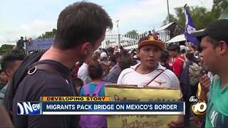 Migrants pack bridge on Mexico's border - Video