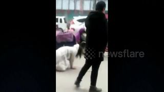 Woman crawls on all fours next to fiancé on busy street in China - Video