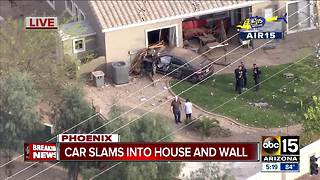 Car slams into Phoenix home, driver hurt - Video