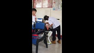 Touching moment two schoolboys help classmate with cerebral palsy during break time