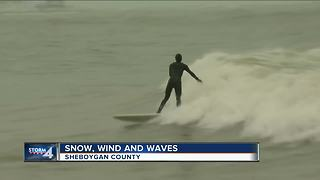 Surfers stay out until sunset during snowstorm - Video
