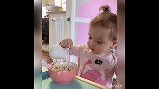 Adorable baby girl eating on her table