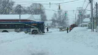 Tow Truck Pulls Erie Bus Through Snowy Street - Video