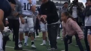 Little girl shows University Of Nevada football players how it's done