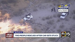 2 people rescued after car gets stuck in wash