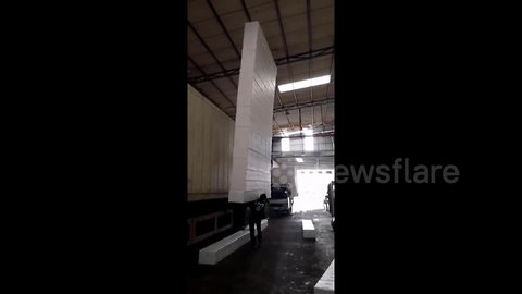 Worker lifts up and balances tower of 18 foam blocks