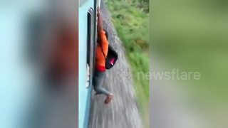 Indian man falls off speeding train when stunt goes wrong - Video