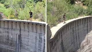 Daredevil skateboarder performs tricks on the edge of huge 200ft dam - Video