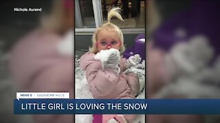 Adorable girl loves eating snow