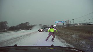 Oncoming motorist slides out of control and nearly strikes a police officer
