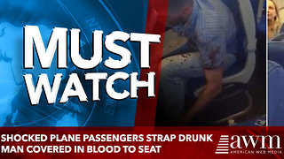 Shocked plane passengers strap drunk man covered in blood to seat - Video