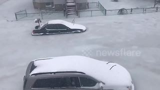 Parked cars trapped in frozen floodwater during US 'bomb cyclone' - Video