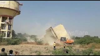 Narrow escape for driver after water tank falls on excavator during demolition - Video