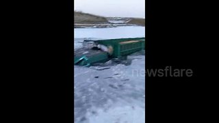 Transport lorry gets stuck in frozen river - Video
