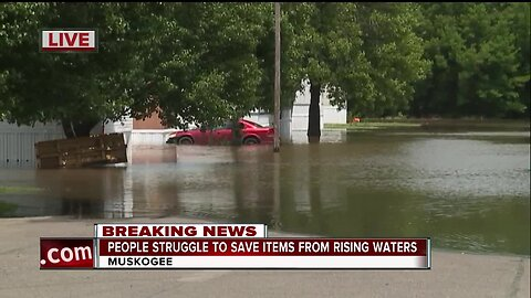 People struggle to save items from rising waters