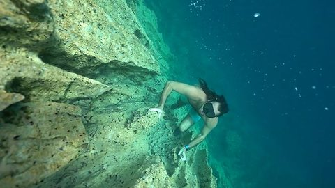 Underwater rock climber scales sheer wall of limestone